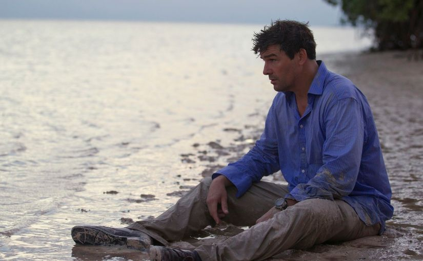 Kyle Chandler's John Rayburn sits stunned and exhausted on the shore